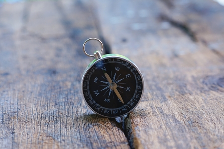 Retro compass on vintage wooden table background with smooth blur background, copy space 免版税图像