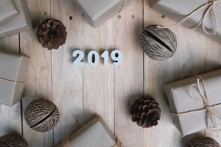 Happy new year 2019 background concept from top view, gift and pine cone decoration on vintage wooden background, copy space Stok Fotoğraf