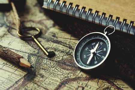 Brújula, llave, lápiz y libro sobre fondo de mapa vintage borroso, tono de color clásico retro Foto de archivo