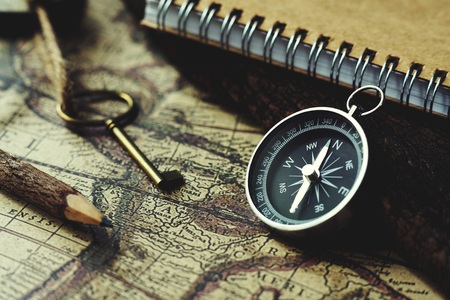 Compass, key, pencil and book on blur vintage map background, retro classic color tone