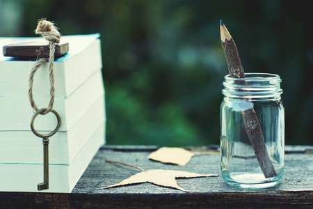 Pencil made of wood in glass bottle, vintage key and book stack on wooden table with morning light and blur green garden background, copy space