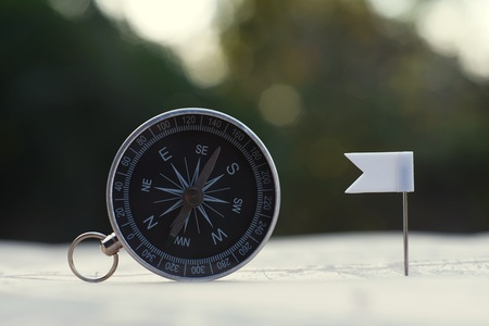 Compass and flag pins on blur vintage world map, journey concept, copy space Stock Photo
