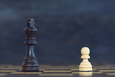 King encounters against powerful pawn in chess game, business competitive concept, copy space