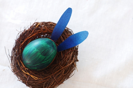 Easter egg painted into bunny face with long and fold ear, Easter holiday concept, fancy eggs, copy space