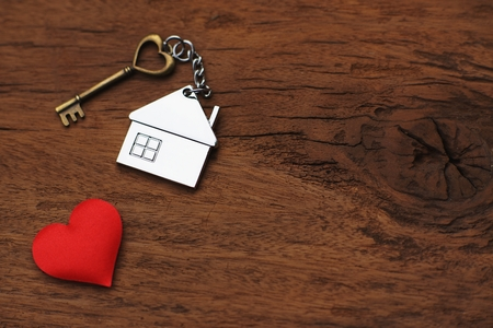 House key with home keyring decorated with mini red heart on wood texture background, sweet home concept, copy space Stock Photo