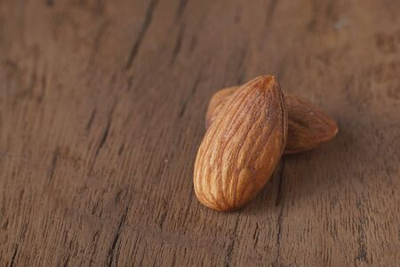 Almond nut in wood bowl on wooden table with green leaf background, copy space