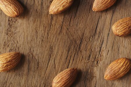 Almond nut in wooden bowl on wooden table with green leaf background, copy space