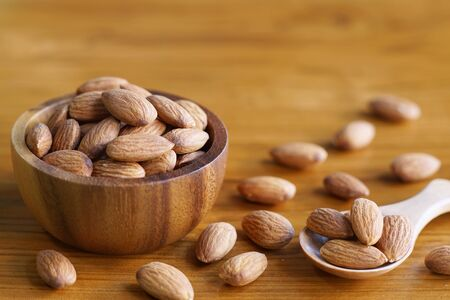 Almond nut in wood bowl on wooden table background, copy space 版權商用圖片