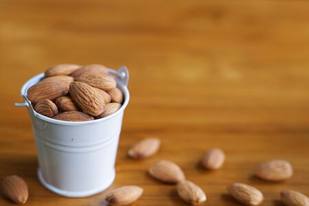 Almond nut in white can on wooden table background, snack concept, copy space 版權商用圖片