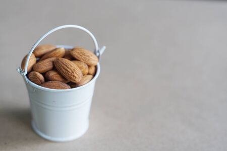 Almond nut in white can and green leaf on wooden table background, copy space 版權商用圖片