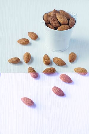 Almond nut in white on white wooden table background, copy space