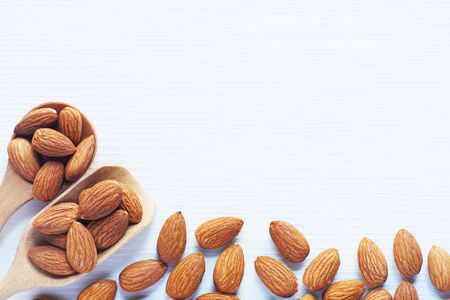 Almond nut in white on white wooden table background, copy space, almond background concept