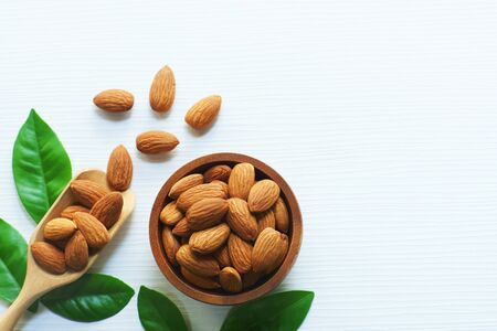 Almond nut in wood bowl and green leaf on white wooden table background, copy space 版權商用圖片