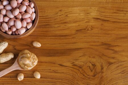 Peanut in wooden bowl on classic wooden table background, peanut butter, copy space