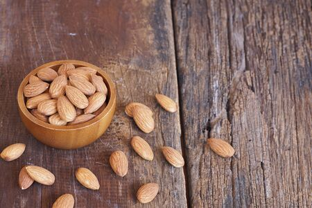Almond nut in wooden bowl on classic wooden table background, copy space