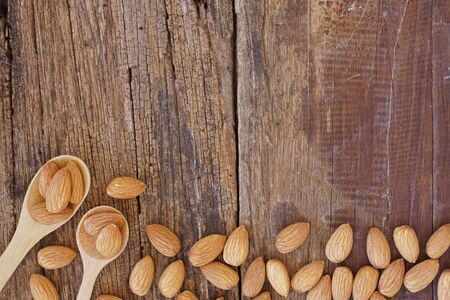 Almond nut in wooden spoon on classic wooden table background, copy space