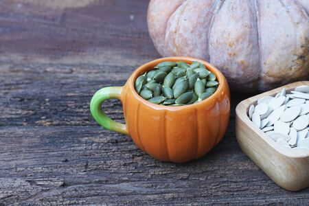 Pumpkin grain in wooden bowl and fresh pumpkin fruit on classic wooden table background, cereal, copy space