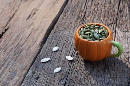 Pumpkin grain in pumpkin cup on classic wooden table background, cereal, copy space