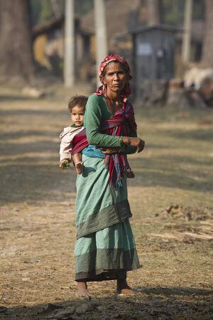 gente pobre: Mujer Tharu llevando a su niño, Bardia, Nepal