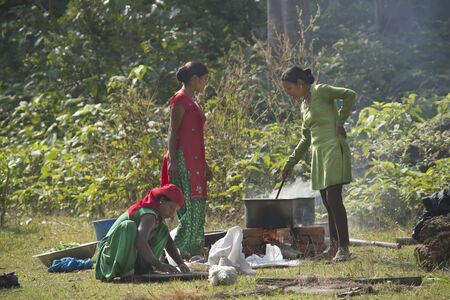 nepali: Nepali Tharu women cooking food in the forest, Bardia, Nepal