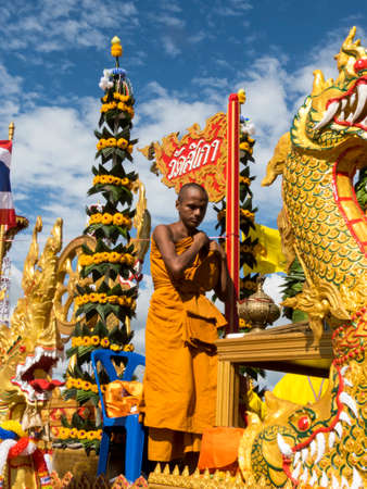 scarry: Buddhist monk on a float, Trang, Thailand