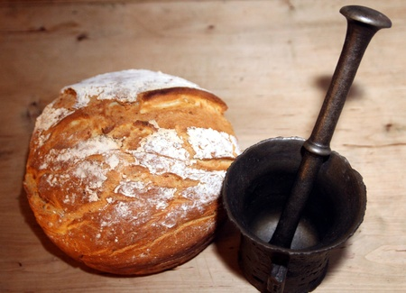 newly baked: Old iron mortar in front of newly baked peasant bread