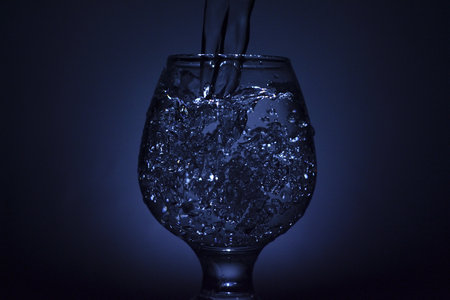Abstract composition for designers with bar glass for cognac and flow jet of spirit with flash sparks
