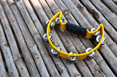 yello: yello tambourine on wooden floor