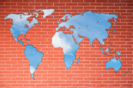 World map on brick wall and blue sky photo