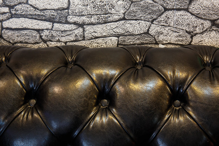 leather sofa: stone wall paper and  Black leather sofa Stock Photo