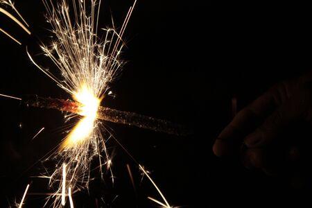 Sparklers (Phooljhari) in a hand on black background on Diwali photo