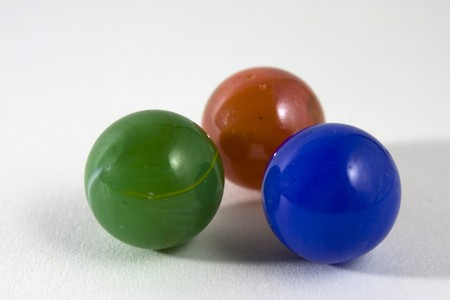 Three shiny colourful glass marbles on a white background photo