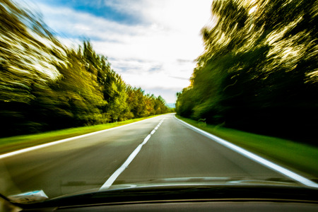 A car speeding down the road that is blurred. Stock Photo