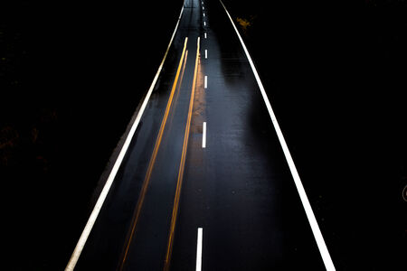 Road with car at night and blurry lights showing speed and motion Stock Photo