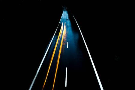 Weg met de auto 's nachts en wazig licht blijkt snelheid en beweging