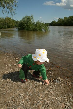 Small girl in green plays ashore rivers Stock Photo