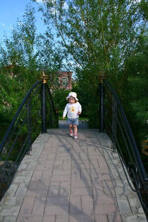Small child girl walking in urban park