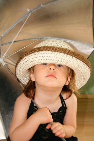 Small pretty girl with umbrella and hat