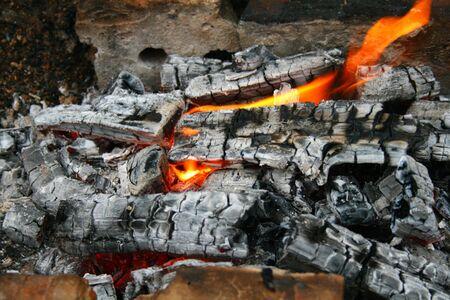 The light orange flame on black charcoal photo