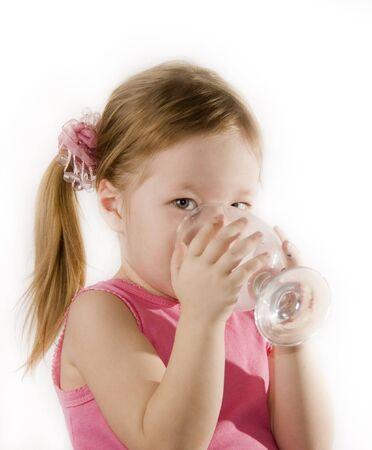 小さな女の子がガラスから水を飲んでいます。 写真素材