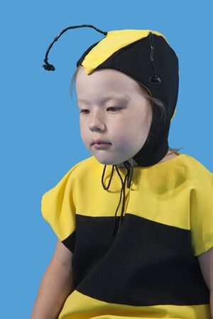 Small girl is dressed at bee costume on blue background photo