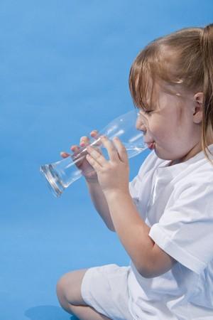 小さなかわいい女の子は、青い背景に水を飲むです。 写真素材