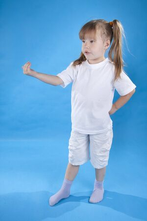 beckon: Small serious girl is posing isolated on blue background