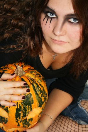 Adorned girl to Halloween c by pumpkin in the hands Stock Photo - 2879095