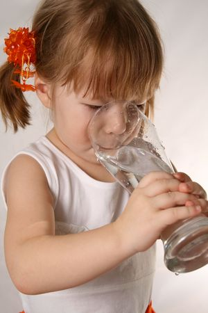 The small girl is drinking water from glass. Stock Photo