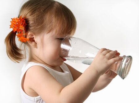 The small girl is drincking water from glas.