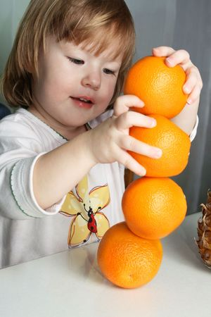 Small girl builds figure from 4 oranges photo