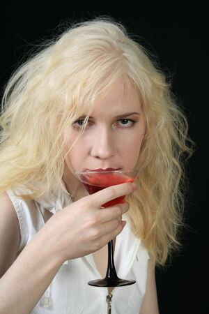 Young blond woman holds martini against the black background photo