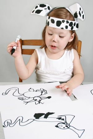 The small girl with dalmatian mask sketches the dog Stock Photo