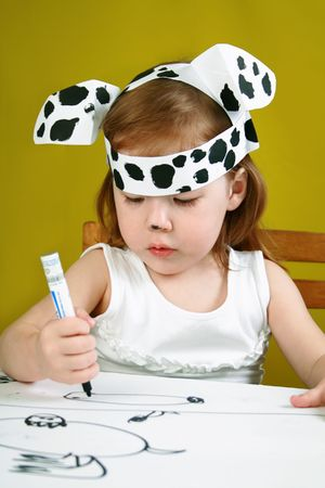 The small girl with dalmatian mask sketches the dog photo